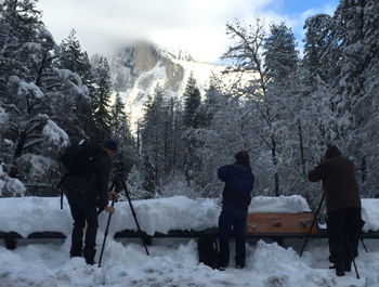 photographers standing in snow on a bridge with Half Dome in their photo