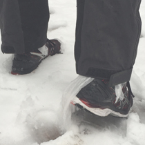 two shoes with plastic bags in them, then feet, walking in snow