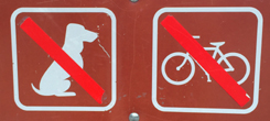 sign with an image of a dog with a red diagonal stripe through it, and an image of a bike with a diagonal red stripe through it