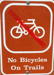 sign with an image of a bike with a diagonal red slash though it and the words No Bicycles On Trails