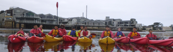 13 students in kayaks in a row