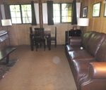 room with large couch, small table and chairs