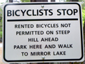 sign that says bicyclists stop, rented bikes not permitted on steep hill ahead, park here and walk to mirror lake