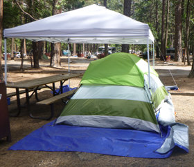 dining canopy partially over a picnic table and tent