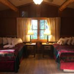 2 double beds, nightstands with lamps, window in a cabin bedroom