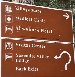 sign with arrows and village-store-medical-clinic-Ahwahnee-hotel-visitor-center lodge and park exits