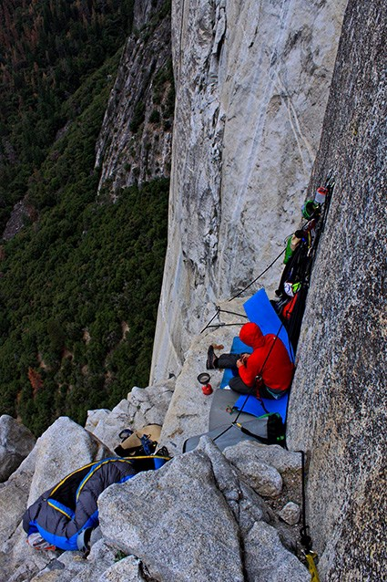 climber sitting on a ledge on a cliff, with sleeping bag nearby