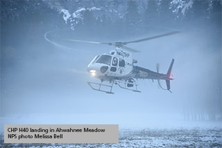 helicopter landing on meadow in foggy winter conditions