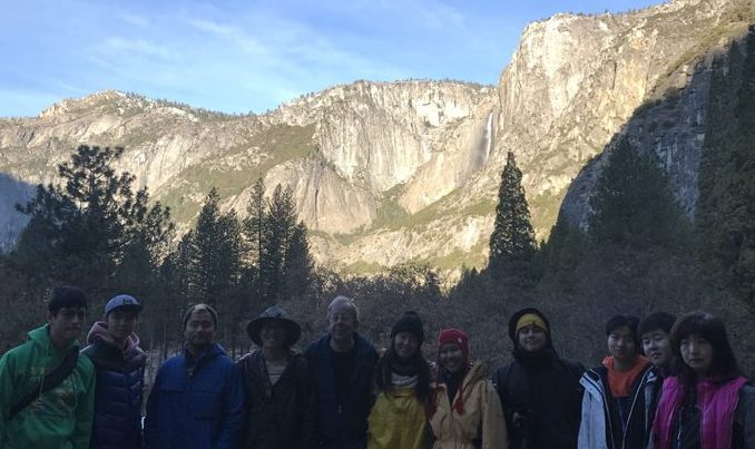 12 people in a line with Yosemite cliff behind