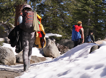 3 hikers, one with many jackets hanging from her pack
