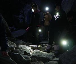 hikers in dark with flashlight beams