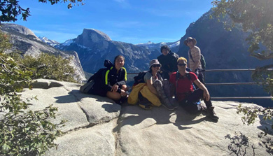 people sitting on a large rock with Half Dome in Background