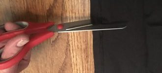 scissors cutting into fabric edge