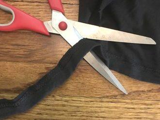 scissors cutting a waistband off a t-shirt