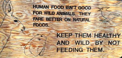 sign says human food isn't good for wild animals they fare better on natural foods