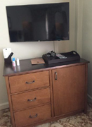 dresser with television above on wall