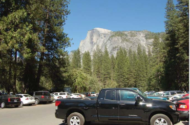 cars in parking lot with Half Dome beyond