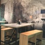table with benches, climbing routes on wall