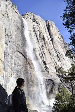 woman turns to look at Yosemite Fall