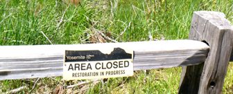 sign on a fence says area closed restoration in progress