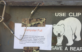 dumpster with sign that it is full