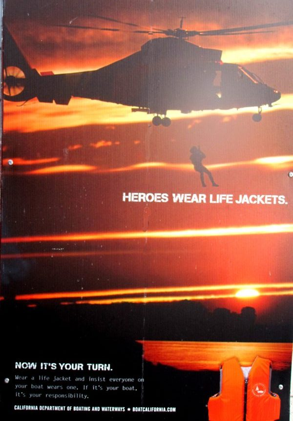 a poster with a rescuer hanging from a helicopter that says heroes wear lifejackets