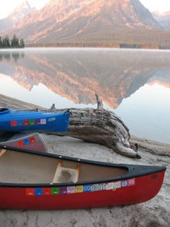 2 canoes and a kayak on a beach