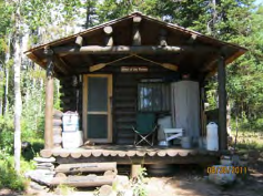 cabin with roof that extends over front porch