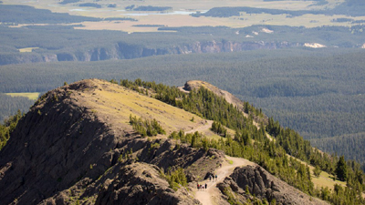 people on trail nearing top of peak