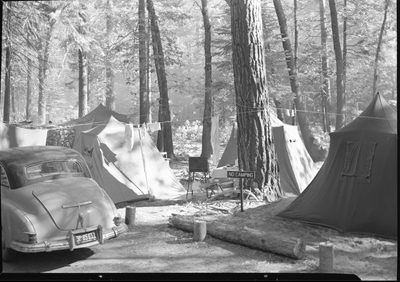 "tents in area that has a sign ""no camping"""