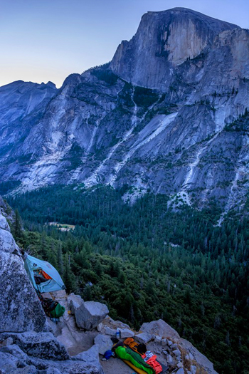 small tent and sleeping bags on cliff with Half Dome beyond