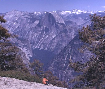 person sitting on El Capitan summit looking towards peaks beyond