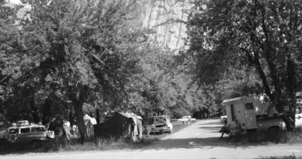 cars, camper,  tents in parking lot