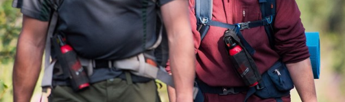 two people with bear spray harnesses around their chests