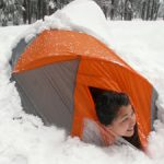 girl looks out from a snow covered tent