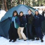 four women standing in front of a huge tent