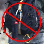 bear spray hanging from back side of a pack, out of reach in an emergency