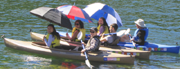 three women with large umbrellas at the front of three kayaks, with three men behind them paddling
