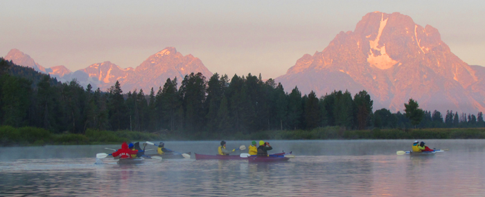 kayakers on river with mountains pink with sunrise