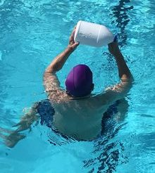man holding a bottle overhead while treading water