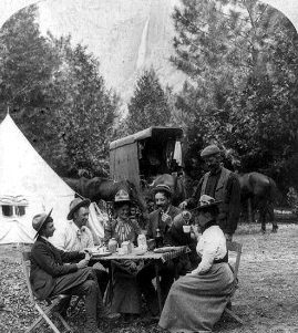 people seated at table. tent and Yosemite falls in background