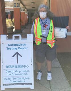 Mary Donahue holding award next to Covid testing sign