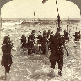beach goers, in swimsuits, wading in the water by holding onto ropes