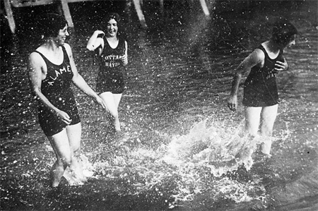 three laughing women having a water fight