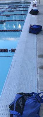 swim gear in bags at pool edge