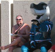 sharkie mascot and lifeguard sitting on bench