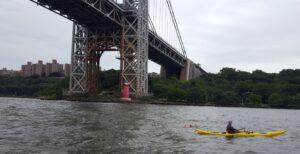 swimmer and kayaker under bridge